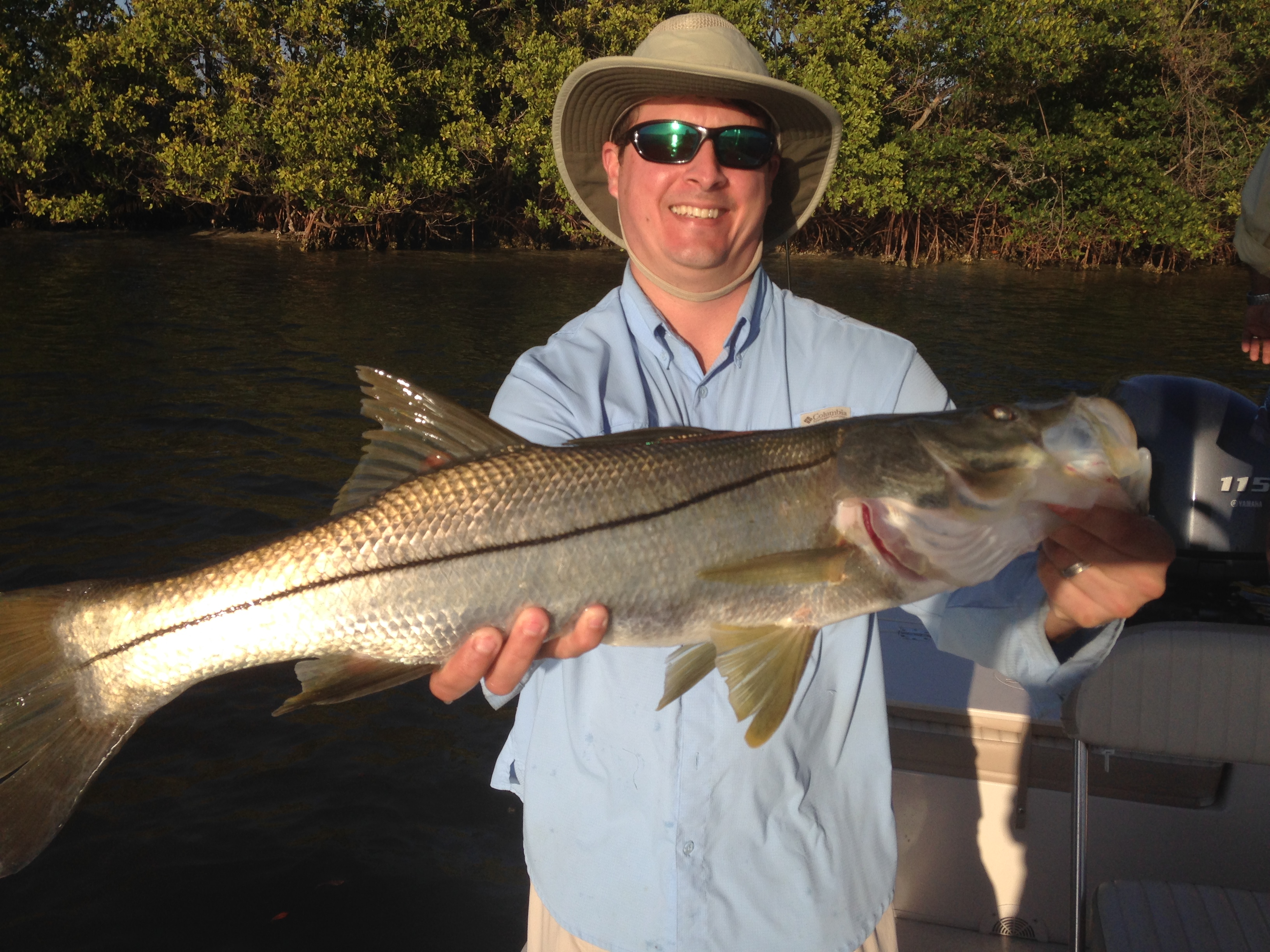 angler holding a fresh caught snook ot of new port richey on a charter